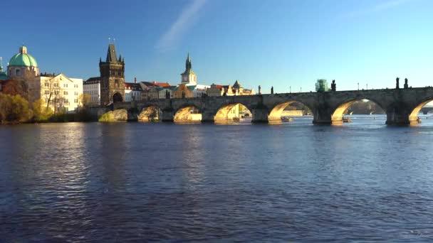 záběr na Karlův most a tekoucí řeku Vltavu ve středu Prahy při západu slunce obloha je v České republice modrá