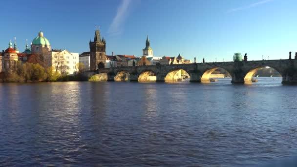 statický záběr na Karlův most a tekoucí řeku Vltavu ve středu Prahy při západu slunce obloha je v České republice modrá