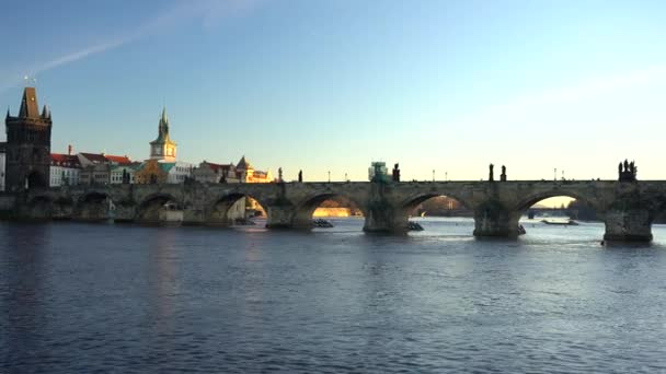 pohybující se záběr na Karlův most a tekoucí řeku Vltavu ve středu Prahy při západu slunce obloha je v České republice modrá