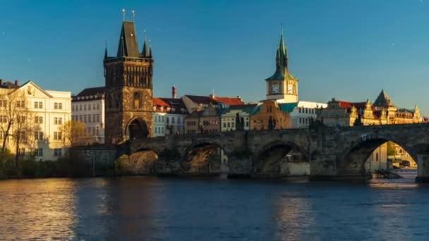 pohybový čas lapse záběr na pohled na Karlův most a tekoucí řeku Vltavu uprostřed Prahy při západu slunce obloha je v České republice modrá