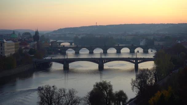pohled na tekoucí vltavu a mosty na řece při západu slunce v centru Prahy na podzimní obloze je zbarvený sluncem