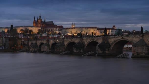časová prodleva tekoucí řeky Vltavy a Karlova mostu z roku 1402 a v pozadí Pražského hradu a katedrály sv. Víta v centru Prahy v noci v České republice