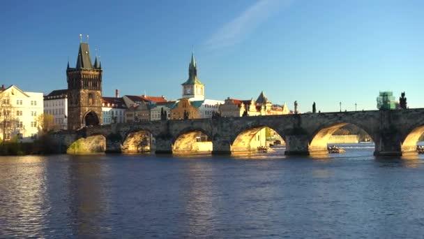 pohybující se záběr vlevo a pohled na řeku Vltavu a staré kameny Karlův most v centru Prahy v létě při západu slunce