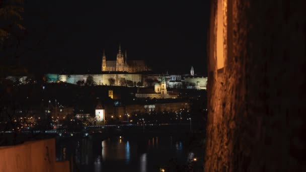 včasné osvětlení Pražského hradu a kostela Nejsvětější uvítání. pohled přes starou osvětlenou hradní pevnost ze 17. století tekoucí řeka Vltava a světla z aut v noci v centru