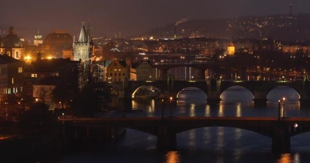 časový odstup pohled na starý kámen ozářený Karlovým mostem a starou kamennou věží a světlo pouličních světel se odráží na hladině Vltavy