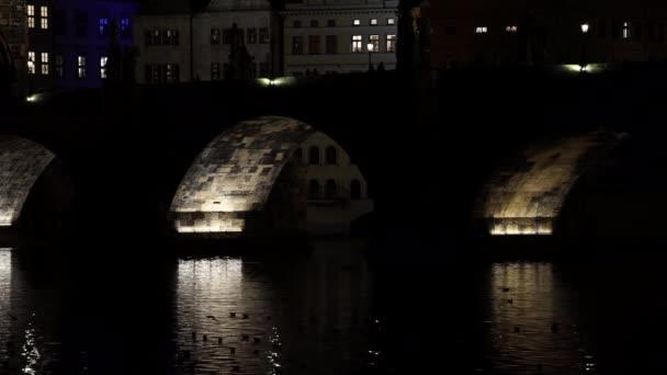 Statische Ansicht der beleuchteten Karlsbrücke aus Stein und des fließenden Flusses Moldau und Beleuchtung der Straßenbeleuchtung im Zentrum von Prag in der Tschechischen Republik bei Nacht