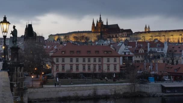 statický pohled na osvětlený kámen Karlův most a tekoucí řeku Vltavu a světla z pouličního osvětlení v centru Prahy v České republice v noci