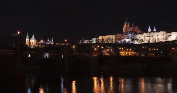 časový odstup Pražského hradu a Karlova mostu a tekoucí vltavy v noci v centru Prahy a světla z pouličního osvětlení
