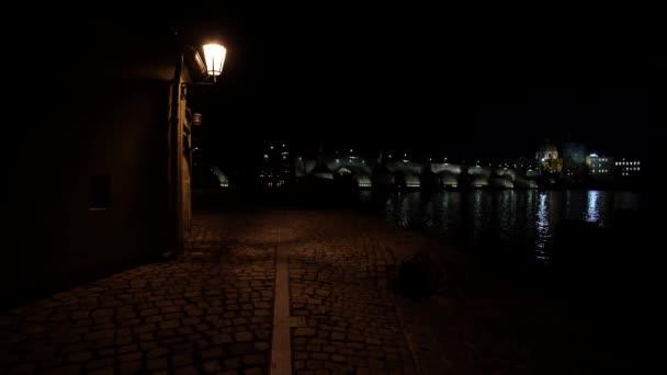 Straßenbeleuchtung und gepflasterter Bürgersteig für Fußgänger und im Gegenzug ein nächtlicher Blick auf die Karlsbrücke und ihre nächtliche Beleuchtung und den fließenden Fluss Moldau im Zentrum von Prag