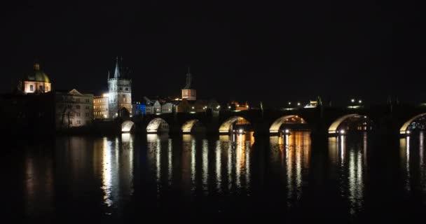 noční pohled na Karlův most a jeho noční osvětlení a tekoucí řeku Vltavu v centru Prahy