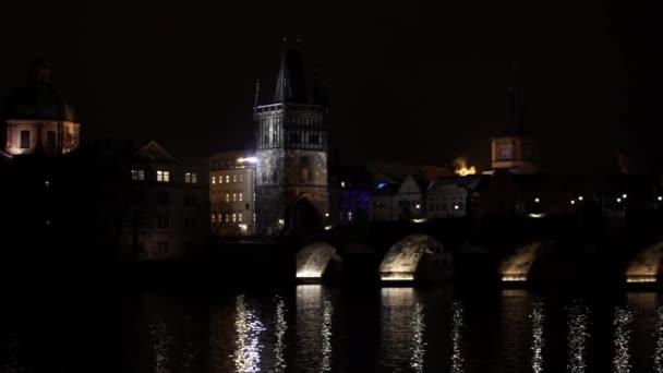 zpomalený noční pohled na Karlův most a jeho osvětlení v noci a tekoucí řeku Vltavu v centru Prahy