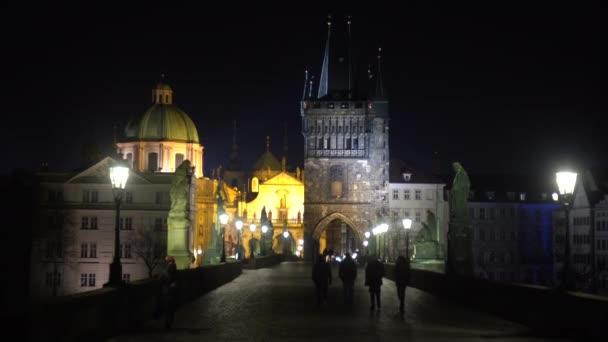 pouliční osvětlení a sochy na kamenném Karlově mostě v noci a siluety chodců na mostě v noci v centru Prahy a ptáků na obloze