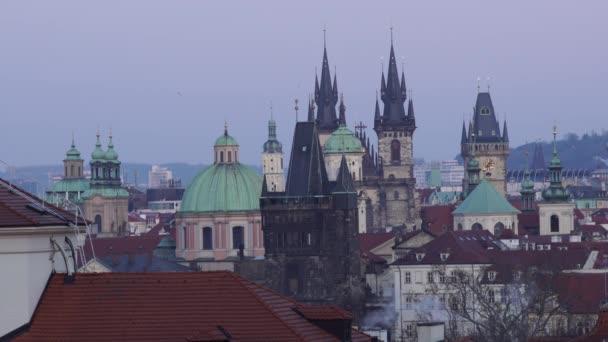 pohled na střechy budov a věží v Praze a kouř z komína v zimě roku 2021 při západu slunce