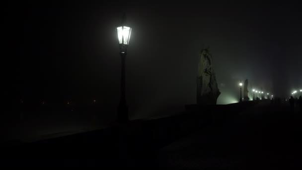 Bewegungsblick Licht in die Laterne der Straßenbeleuchtung auf der Karlsbrücke und Nebel in der Nacht und Silhouetten von Fußgängern und Läufern auf dem Kopfsteinpflaster auf der Brücke im aufsteigenden Nebel in der Nacht.