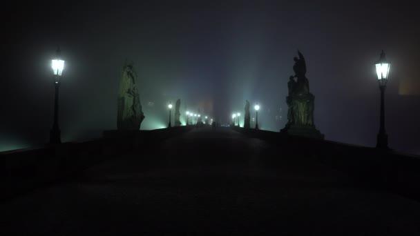Statische Sicht Licht in die Laterne der Straßenbeleuchtung auf der Karlsbrücke und Nebel in der Nacht und Silhouetten von Fußgängern auf dem Kopfsteinpflaster in Prag.