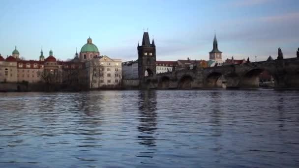 pohybový pohled na tekoucí řeku Vltavu a věž na Karlově mostě při západu slunce v centru Prahy