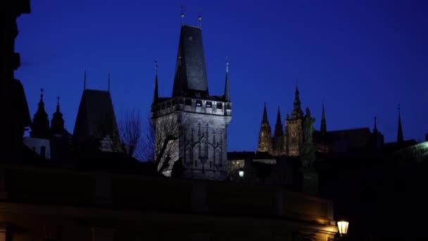 pohled na pouliční osvětlení siluet vězňů na Karlově a na pozadí Pražského hradu a katedrály sv. Víta za soumraku.
