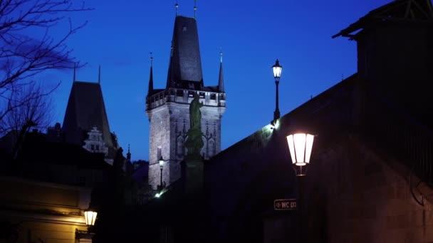 Blick auf die Straßenbeleuchtung eines Turms auf der Karlsbrücke im Morgengrauen, blauer Himmel
