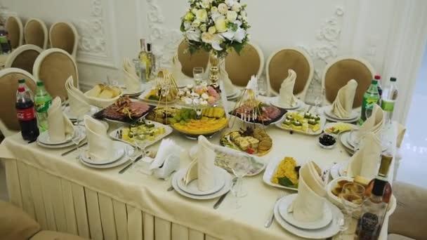 Obdélníkový stůl v drahé restauraci je servírován se stříbrnými příbory, ubrousky a nádobím z jídelního lístku a uprostřed stolu je zlatá váza s květinami, kolem jsou židle s měkkými sedadly
