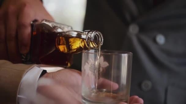 Dva kavkazští muži, formálně a elegantně oblečení v oblecích a bílých košilích, stojí, jeden drží v ruce brýle a druhý nalévá hnědý alkohol z láhve whisky.