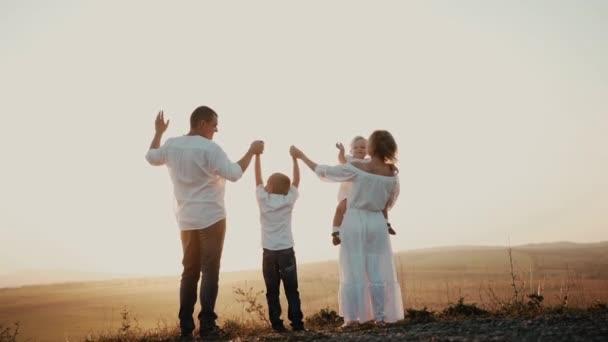 Šťastná rodina při západu slunce. Máma táta a syn se drží za ruce na obzoru a rodiče vychovávají zábavné děti. Žena drží malou dcerku, která mává rukou v kameře a pak posílá vzdušné polibky otci