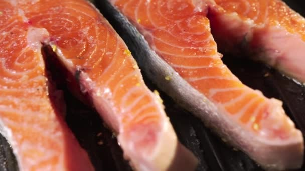 Nyers vörös hal darabok hevernek egy elektromos grillen. A lazac steak a vendégek rendelkezésére áll. Zsír túlmelegszik és gurgles a magas hőmérsékletű alkotó buborékok. Közelkép