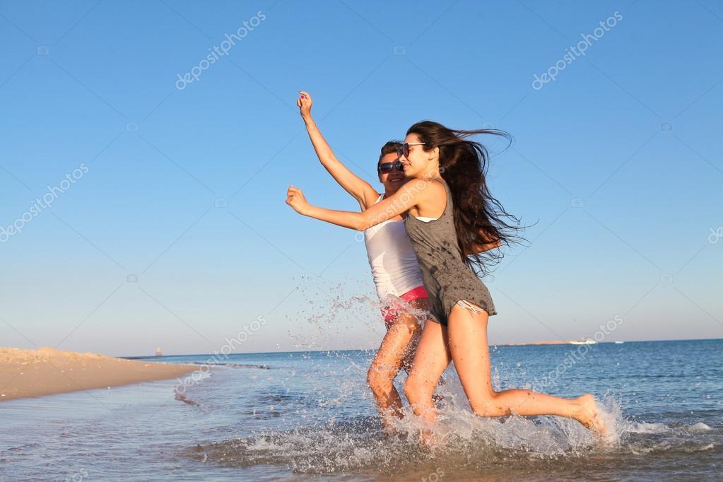 girls running happily on beach