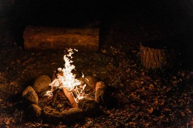 Warm and cozy outdoor fireplace at night with black background. Authentic fire with warm colors. Wild fire.
