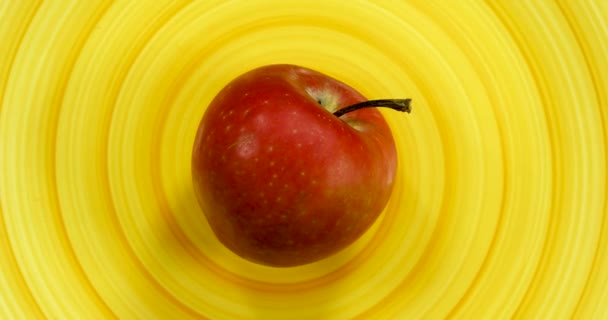 Red apple rotating on a spiral yellow plate, isolated fruits 4k.