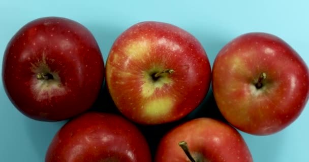 Red apples rotating on light blue background, isolated fruits 4k.