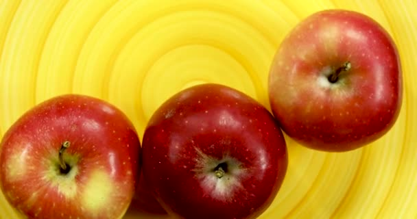 Red apples rotating on a spiral yellow plate, isolated fruits 4k.