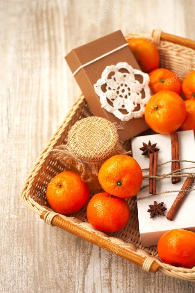 Korb mit Weihnachtsgeschenke: Honig, Mandarine und eine Box mit Sou ...