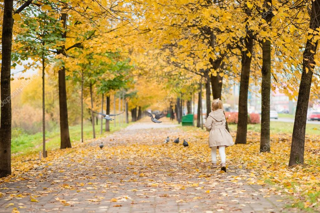 Beautiful little girl runs for birds in autumn park