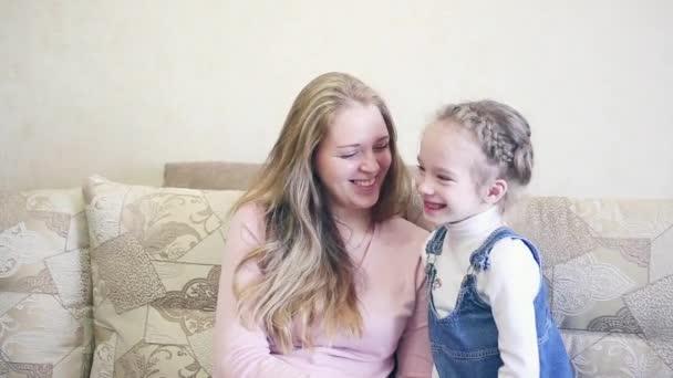 Little girl kisses mother cheek, closeup view at sofa