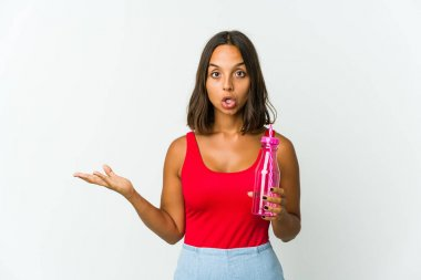 Young latin woman holding a milkshake isolated on white background impressed holding copy space on palm.