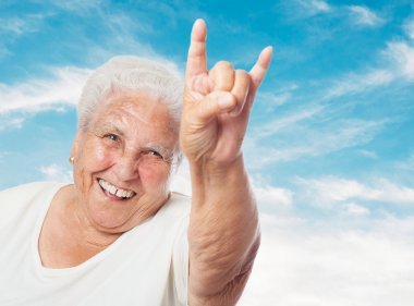 Old woman showing rock symbol