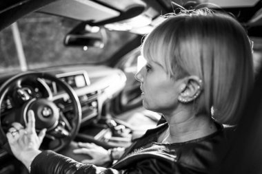 black and white portrait of beautiful blonde woman in car at parking lot