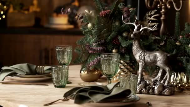 Tischdekoration Weihnachten, Banketttisch mit Gläsern vor dem Servieren, Großaufnahme Weihnachtstisch mit saisonaler Dekoration, Kristallgläser und dekorativer Hirsch