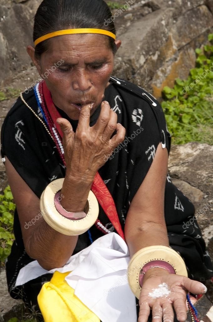 woman in traditional clothes using beatlenut