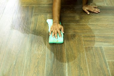 Worker cleaning floor tile after grouting tiles with sponge