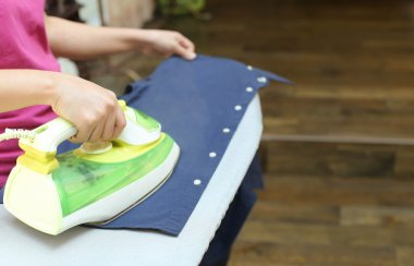 Woman ironing a blue shirt