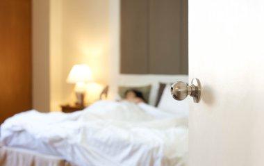 Sleeping woman resting in bed with door open