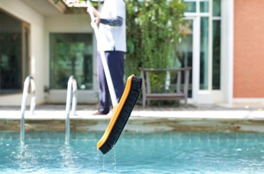 Mna is cleaning a swimming pool with a brush