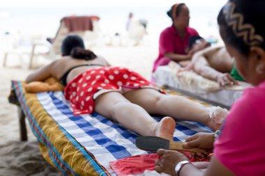 Woman having foot scrub on the beach