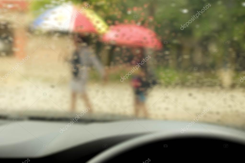 Blurry concept  people walking in the rain with umbrella
