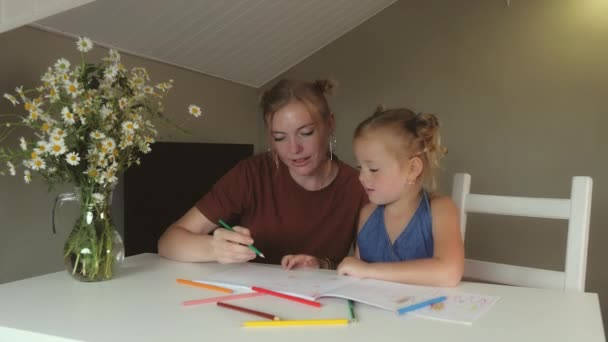 Mother and her daughter draw with colored pencils in large album at home
