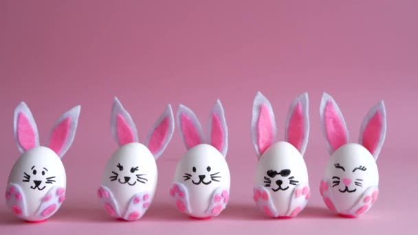 Eggs painted as rabbits with different emotions on a pink background.