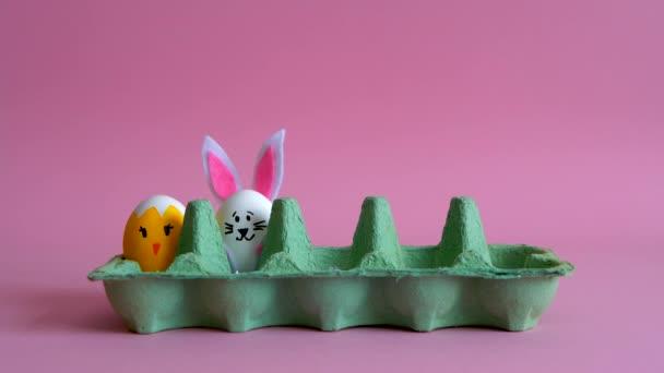 Krabička od vajec se plní malovanými vejci, zajíčky a kuřaty na růžovém pozadí