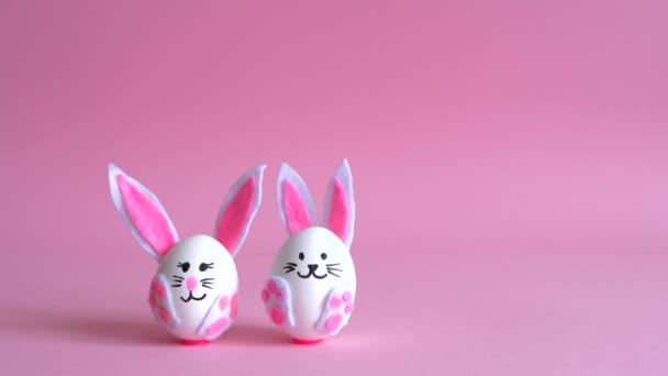 Velikonoční zajíčci z vajec na růžovém pozadí.
