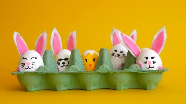 Prázdná krabička od vajíček naplňuje malovanými vejci, zajíčky a kuřaty na žlutém pozadí